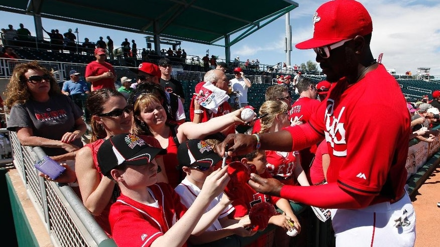 Cincinnati Reds' Brandon Phillips signs autographs before an exhibition baseball game against the Cleveland Indians in Goodyear, Ariz., Thursday, Feb. 27, 2014. (AP Photo/Paul Sancya)