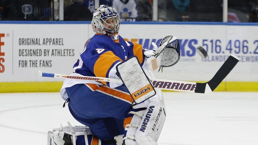 New York Islanders goalie Evgeni Nabokov, of Kazakhstan, deflects a shot during the first period of an NHL hockey game against the Toronto Maple Leafs on Thursday, Feb. 27, 2014, in Uniondale, N.Y. (AP Photo/Frank Franklin II)