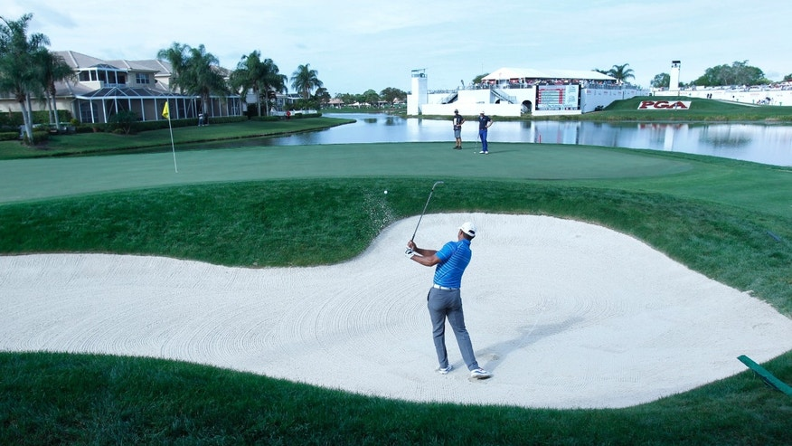 Golfer Tiger Woods hits out of a bunker on the 17th hole during the first round of the Honda Classic golf tournament, Thursday, Feb. 27, 2014, in Palm Beach Gardens, Fla. (AP Photo/Wilfredo Lee)