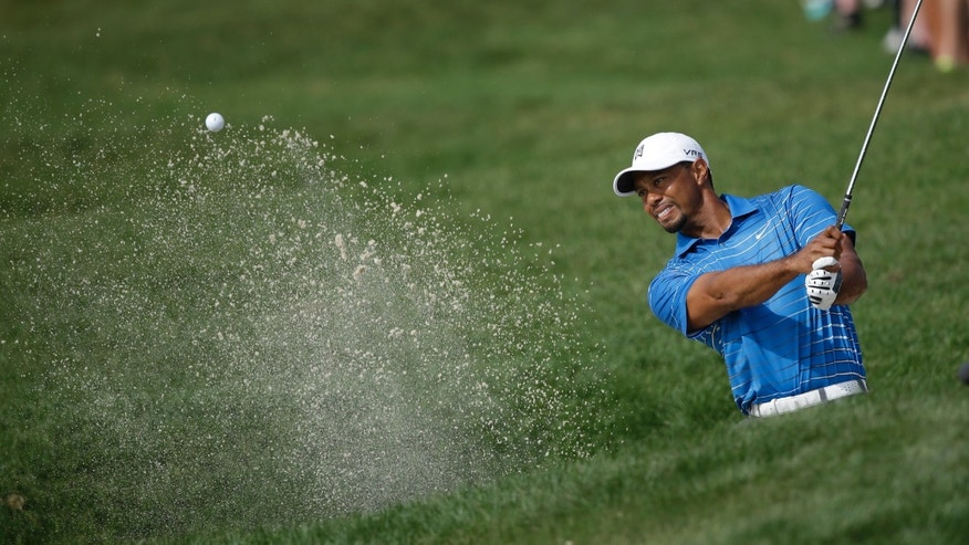 Tiger Woods hits out of a bunker on the 18th hole during the first round of the Honda Classic golf tournament, Thursday, Feb. 27, 2014 in Palm Beach Gardens, Fla. (AP Photo/Wilfredo Lee)