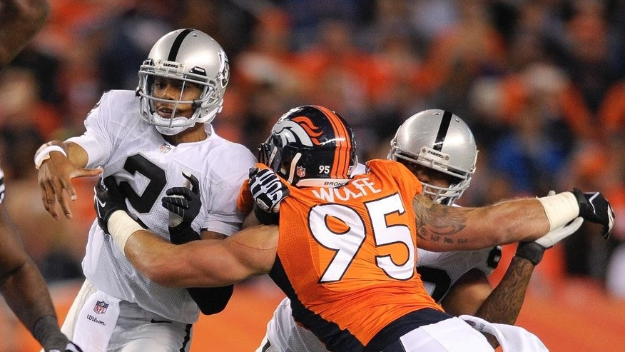FILE - In this Sept. 23, 2013 file photo, Oakland Raiders quarterback Terrelle Pryor (2) is hit by Denver Broncos defensive end Derek Wolfe (95) after throwing a pass in the second quarter of an NFL football game, in Denver. Wolfe says he's finally healthy after suffering a seizure in November that doctors now believe was related to the spinal cord injury he suffered in the preseason. In an interview outside his home with Denver television stations KCNC and KMGH this week, the Broncos' defensive lineman said he's back up to 280 pounds, having regained 20 of the 30 pounds he lost last season, and was ready to return to training next week. (AP Photo/Jack Dempsey, File)