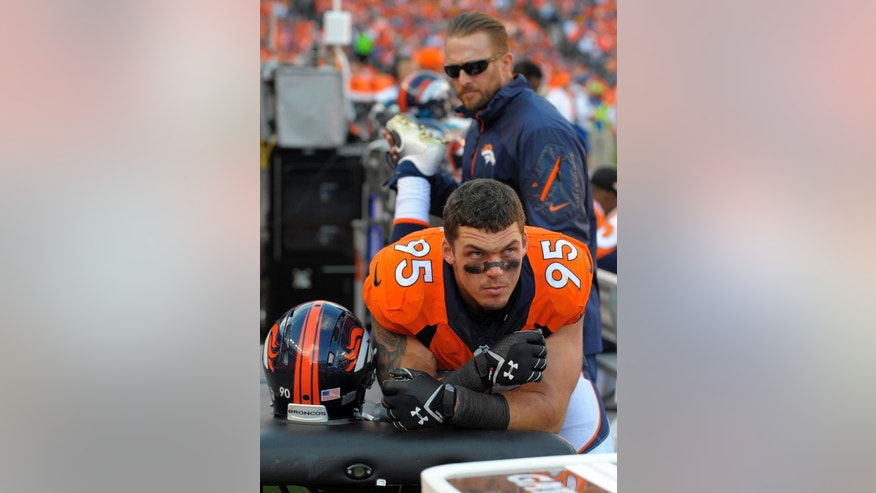 FILE - In this Oct. 27, 2013 file photo, Denver Broncos defensive end Derek Wolfe is worked on by a trainer during an NFL football game against the Washington Redskins  in Denver. Wolfe says he's finally healthy after suffering a seizure in November that doctors now believe was related to the spinal cord injury he suffered in the preseason. In an interview outside his home with Denver television stations KCNC and KMGH this week, the Broncos' defensive lineman said he's back up to 280 pounds, having regained 20 of the 30 pounds he lost last season, and was ready to return to training next week. (AP Photo/Jack Dempsey, File)