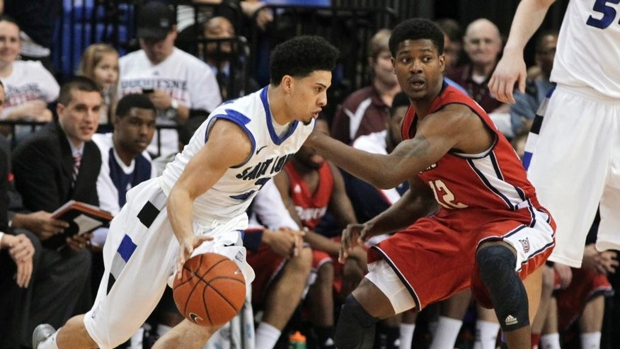 Saint Louis' Austin McBroom (2) drives around Duquesne's Desmond Ridenour (32) during the first half of an NCAA college basketball game, Thursday, Feb. 27, 2014, in St. Louis.(AP Photo/Tom Gannam)