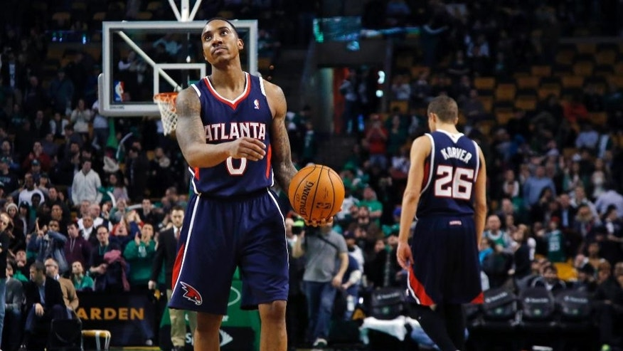 Atlanta Hawks guard Jeff Teague (0) holds the ball while teammate Kyle Korver (26) walks off the court as time runs out in the Hawks' 115-104 loss to the Boston Celtics in an NBA basketball game in Boston, Wednesday, Feb. 26, 2014. (AP Photo/Elise Amendola)