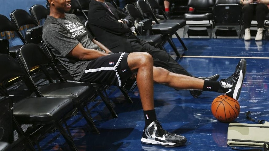 Brooklyn Nets center Jason Collins sits in a courtside seat after warming up for the Nets' NBA basketball game against the Denver Nuggets in Denver on Thursday, Feb. 27, 2014. (AP Photo/David Zalubowski)