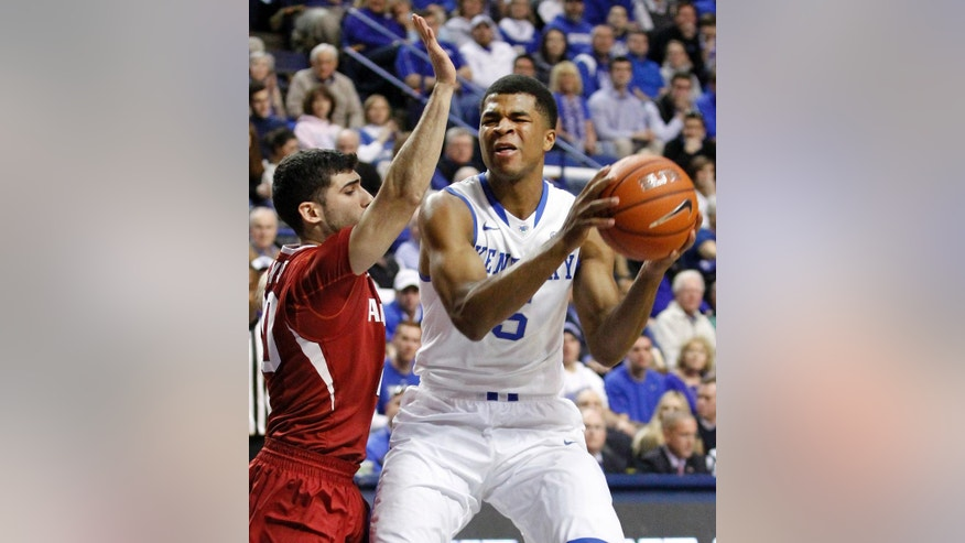 Kentucky's Andrew Harrison (5) is pressured by Arkansas' Kikko Haydar during the first half of an NCAA college basketball game Thursday, Feb. 27, 2014, in Lexington, Ky. (AP Photo/James Crisp)