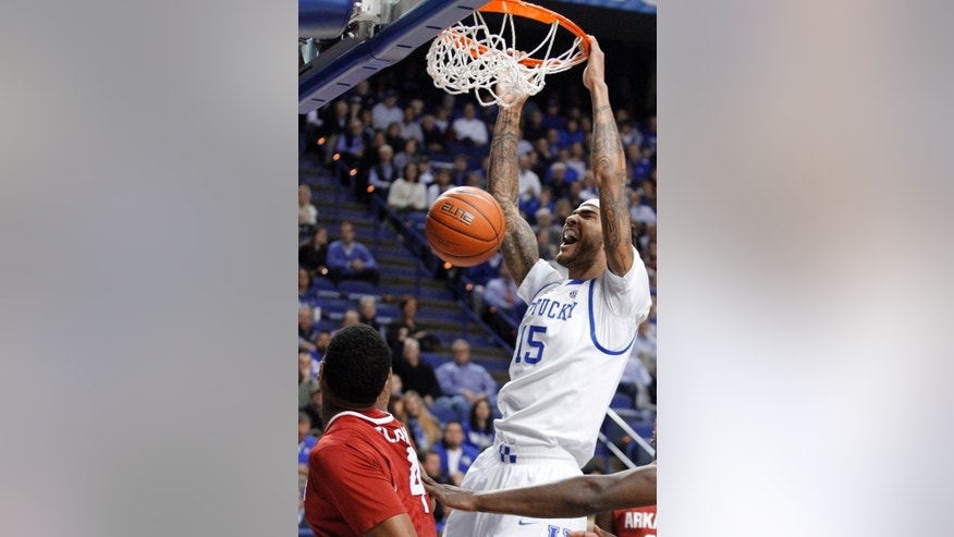 Kentucky's Willie Cauley-Stein (15) dunks next to Arkansas' Coty Clarke (4) during the first half of an NCAA college basketball game Thursday, Feb. 27, 2014, in Lexington, Ky. (AP Photo/James Crisp)