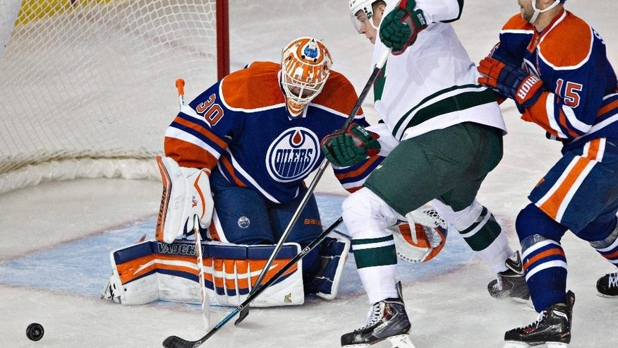 Minnesota Wild's Charlie Coyle (3) is stopped by Edmonton Oilers goalie Ben Scrivens (30) as Nick Schultz (15) defends during second period NHL hockey action in Edmonton, Canada, Thursday, Feb. 27, 2014. (AP Photo/The Canadian Press, Jason Franson)