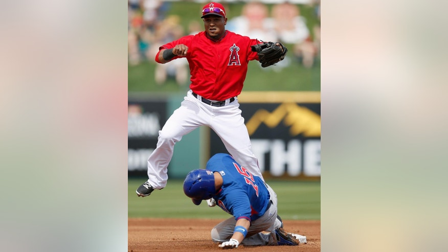Los Angeles Angels' Erick Aybar, top, jumps over Chicago Cubs' Darwin Barney after Barney was forced out at second base in the first inning during a spring training baseball game on Friday, Feb. 28, 2014, in Tempe, Ariz. The Angels won 15-3. (AP Photo/Ross D. Franklin)