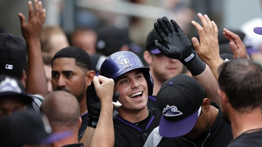 Colorado Rockies' Ryan Casteel, center, is greeted by teammates after hitting a home run against the Arizona Diamondbacks during the third inning in a spring training baseball game Friday, Feb. 28, 2014, in Scottsdale, Ariz. (AP Photo/Gregory Bull)
