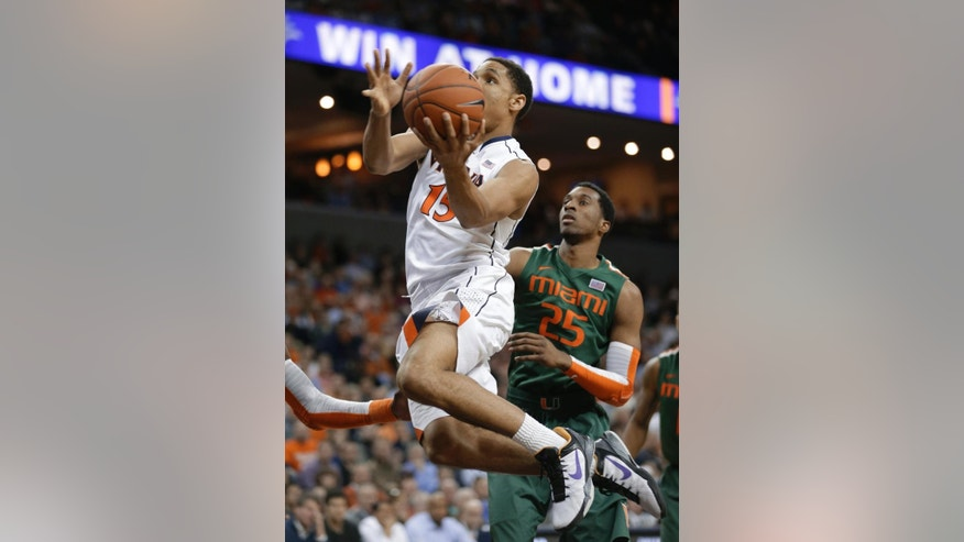 Virginia guard Malcolm Brogdon (15) takes a shot in front of Miami guard Garrius Adams (25) during the second half of an NCAA college basketball game in Charlottesville, Va., Wednesday, Feb. 26, 2014. Virginia won 65-40. (AP Photo/Steve Helber)