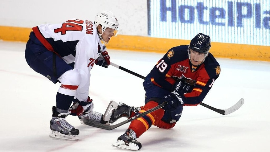 After skating into Washington Capitals' John Carlson (74), Florida Panthers' Scottie Upshall hits the puck away during the second period of an NHL hockey game, Thursday, Feb. 27, 2014, in Sunrise, Fla. (AP Photo/J Pat Carter)
