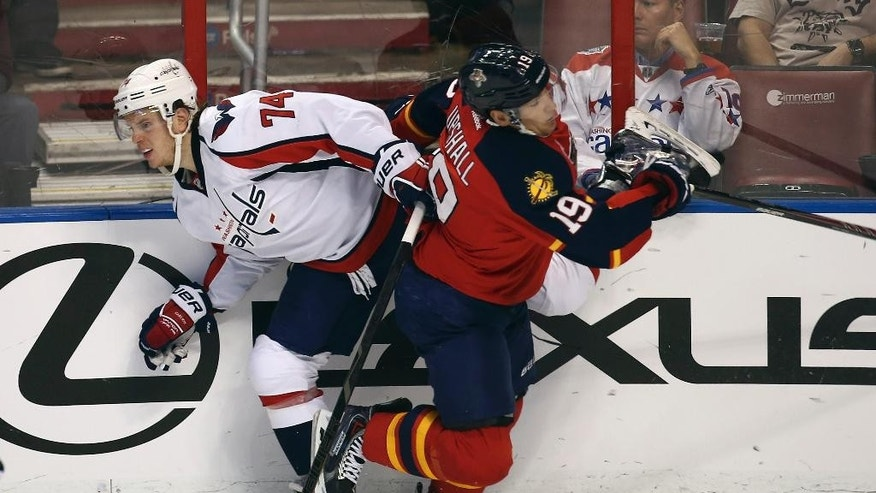 Washington Capitals' John Carlson (74) and Florida Panthers' Scottie Upshall (19) collide during the second period of an NHL hockey game, Thursday, Feb. 27, 2014, in Sunrise, Fla. (AP Photo/J Pat Carter)