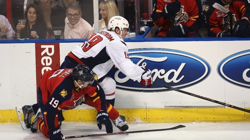 Florida Panthers' Scottie Upshall (19) and Washington Capitals' Nicklas Backstrom (19) vie for the puck during the first period of an NHL hockey game, Thursday, Feb. 27, 2014, in Sunrise, Fla. (AP Photo/J Pat Carter)
