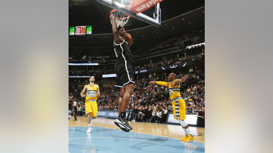 Brooklyn Nets center Andray Blatche, center, dunks as Denver Nuggets guards Evan Fournier, back left, and Randy Foye watch during the first quarter of an NBA basketball game in Denver on Thursday, Feb. 27, 2014. (AP Photo/David Zalubowski)