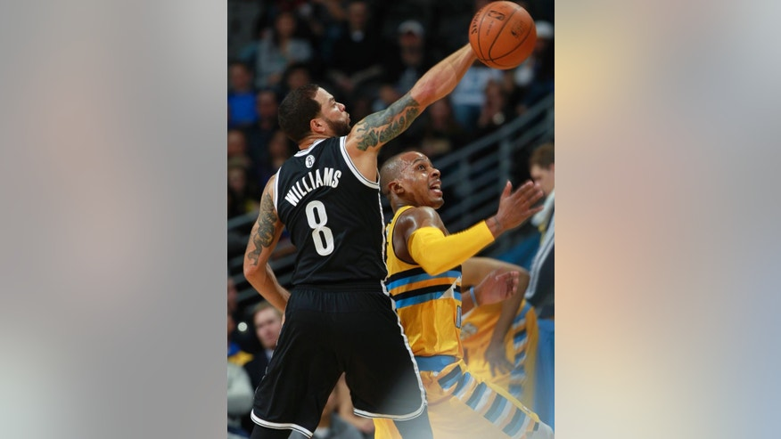 Brooklyn Nets guard Deron Williams, left, deflects a ball away from Denver Nuggets guard Randy Foye during the first quarter of an NBA basketball game in Denver on Thursday, Feb. 27, 2014. (AP Photo/David Zalubowski)