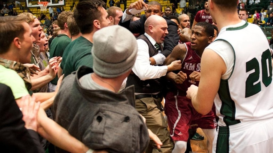 In this Thursday, Feb. 27, 2014 photo, New Mexico State's DK Eldridge, at right center in red and white uniform,  is controlled by security during a brawl involving players and fans who came onto the court when New Mexico State guard K.C. Ross-Miller hurled the ball at Utah Valley's Holton Hunsaker seconds after the Wolverines' 66-61 overtime victory against the Aggies in Orem, Utah.  (AP Photo/The Daily Herald, Grant Hindsley) MANDATORY CREDIT
