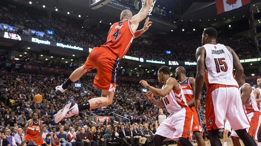 Washington Wizards' Marcin Gortat, center, swings from the hoop as his missed shot rebounds out to Wizards' Martell Webster, left, during first half NBA basketball action against Toronto Raptors in Toronto, Thursday, Feb. 27, 2014. (AP Photo/The Canadian Press, Chris Young)
