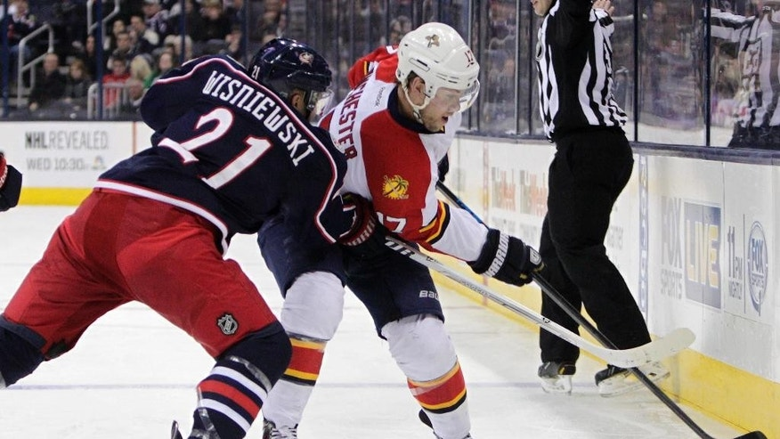 Florida Panthers' Jesse Winchester, right, tries to clear the puck past Columbus Blue Jackets' James Wisniewski during the first period of an NHL hockey game Saturday, March 1, 2014, in Columbus, Ohio. (AP Photo/Jay LaPrete)