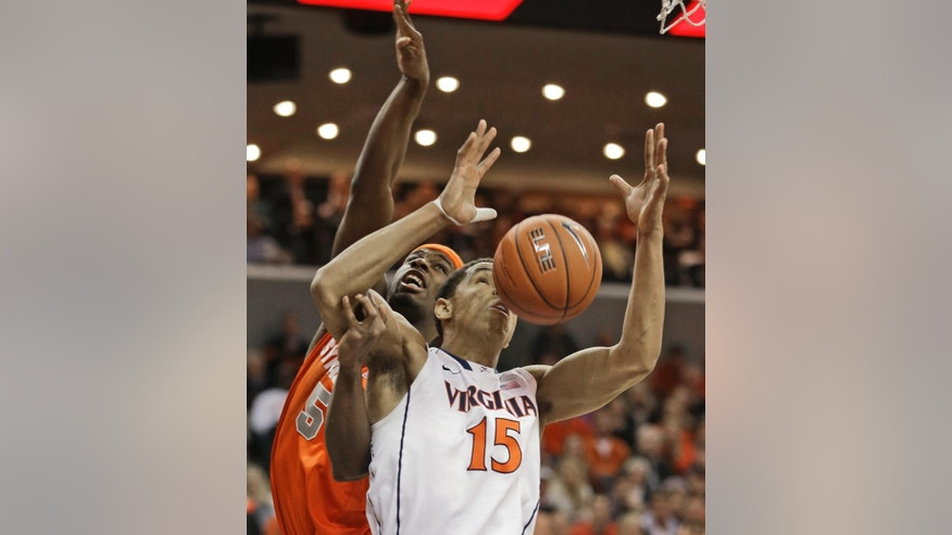 Virginia guard Malcolm Brogdon (15) and Syracuse forward C.J. Fair (5) fight for a rebound during the first half of an NCAA College basketball game in Charlottesville, Va., Saturday, March 1, 2014.  (AP Photo/Steve Helber)