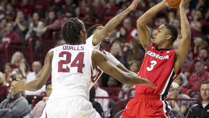 Arkansas guard Michael Qualls (24) defends Georgia guard Juwan Parker (3) during the first half of an NCAA college basketball game on Saturday, March 1, 2014, in Fayetteville, Ark. (AP Photo/Gareth Patterson)