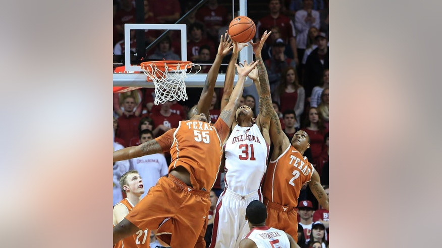 Oklahoma forward D.J. Bennett (31) and Texas center Cameron Ridley (55) and guard Demarcus Holland (2) reach for the ball during the first half of an NCAA college basketball game in Norman, Okla., Saturday, March 1, 2014. (AP Photo/Alonzo Adams)