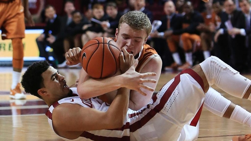 Oklahoma guard Frank Booker, bottom, and Texas forward Connor Lammert scramble for a loose ball during the first half of an NCAA college basketball game in Norman, Okla., Saturday, March 1, 2014. (AP Photo/Alonzo Adams)