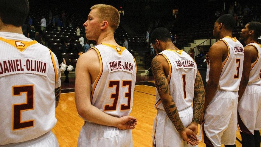 Winthrop basketball players Carlin Bremner (2), Hunter Sadlon (33), Brandon Vega (1) and Christian Farmer (3) wear the first names of children killed in the Newtown, Conn., school shooting on their jerseys during ceremonies before an NCAA college basketball game against Presbyterian in Rock Hill, S.C. on Saturday, March 1, 2014.  (AP Photo/Nell Redmond)