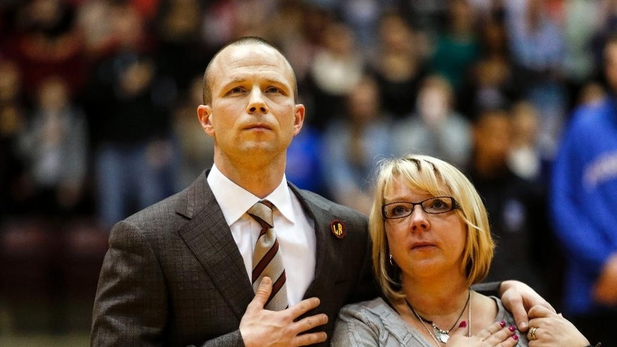 Winthrop basketball coach Pat Kelsey, left, and Becky Kowalski embrace during the National Anthem before a college basketball game between Winthrop and Presbyterian in Rock Hill, S.C. on Saturday, March 1, 2014. Becky Kowalski's seven-year-old son, Chase, was killed in the Newtown, Conn., school shootings. (AP Photo/Nell Redmond)