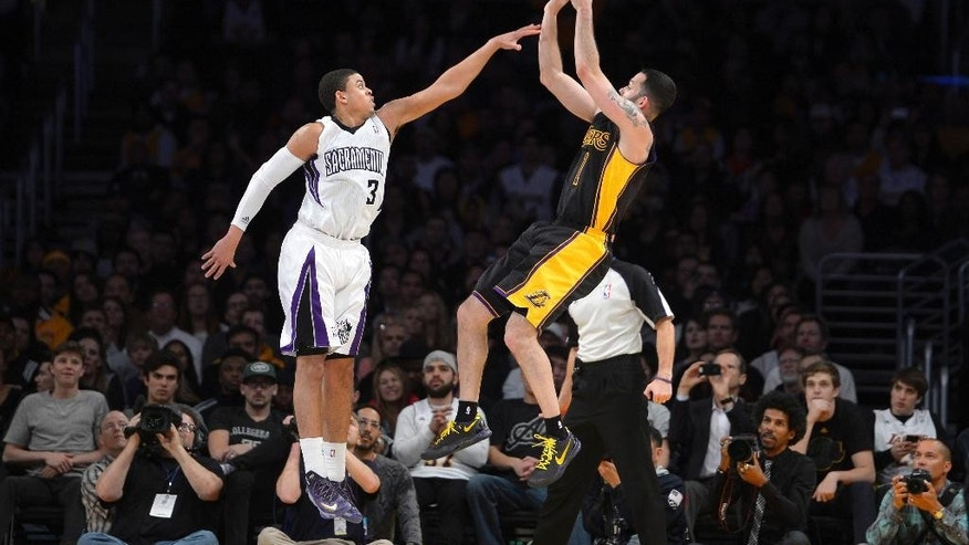 Los Angeles Lakers guard Jordan Farmar, right, puts up a shot as Sacramento Kings guard Ray McCallum defends during the second half of an NBA basketball game, Friday, Feb. 28, 2014, in Los Angeles. (AP Photo/Mark J. Terrill)