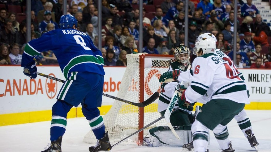 Vancouver Canucks' Zack Kassian, left, has his shot deflect off the side of the net and stay out of the goal as Minnesota Wild goalie Darcy Kuemper, centrt, and Marco Scandella watch during the first period of an NHL hockey game Friday, Feb. 28, 2014, in Vancouver, British Columbia. (AP Photo/The Canadian Press, Darryl Dyck)