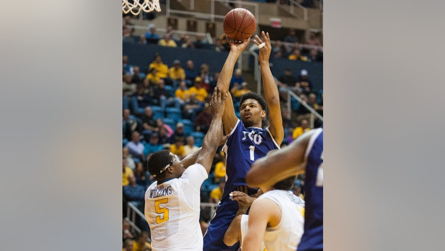 TCU's Karviar Shepherd, right, looks to shoot over West Virginia's Devin Williams during the first half of an NCAA college basketball game Saturday, March 1, 2014, in Morgantown, W.Va. (AP Photo/Andrew Ferguson)