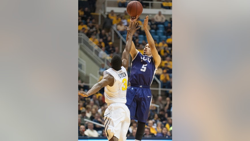 TCU's Kyan Anderson, right, looks to shoot over West Virginia's Juwan Staten during the first half of an NCAA college basketball game Saturday, March 1, 2014, in Morgantown, W.Va. (AP Photo/Andrew Ferguson)