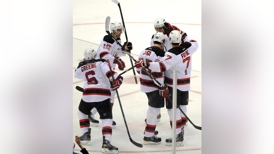 New Jersey Devils' Jaromir Jagr (68) is congratulated by Andy Greene (6), Travis Zajac (19), Dainius Zubrus (8) and Mark Fayne (7) after Jagr scored his 700th goal in the second  period of an NHL hockey game against the New York Islanders on Saturday, March 1, 2014, in Uniondale, N.Y. (AP Photo/Kathy Kmonicek)