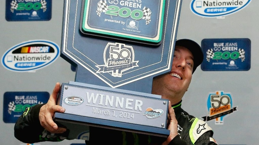 Kyle Busch poses for photographers with the winner's trophy after his victory in a rain-shortened NASCAR Nationwide auto race on Saturday, March 1, 2014, in Avondale, Ariz. (AP Photo/Ross D. Franklin)