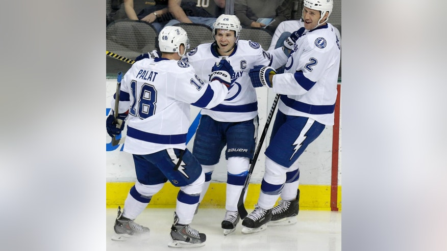 Tampa Bay Lightning right wing Martin St. Louis, center, celebrates scoring a goal with teammates Ondrej Palat (18) and Eric Brewer (2) during the first period of an NHL hockey game against the Dallas Stars Saturday, March 1, 2014, in Dallas. (AP Photo/LM Otero)