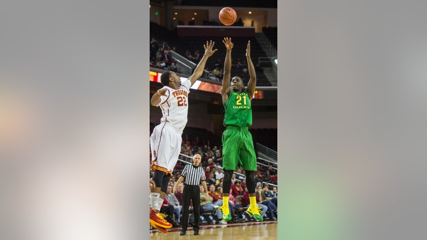 Oregon guard Damyean Dotson, right, shoots against Southern California guard Byron Wesley during the first half of an NCAA college basketball game Saturday, March 1, 2014, in Los Angeles. (AP Photo/Ringo H.W. Chiu)