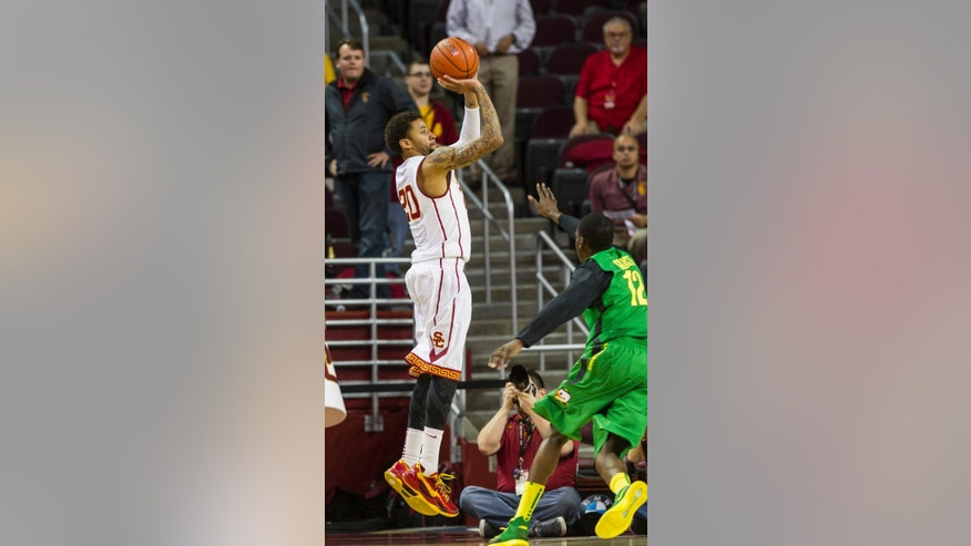 Southern California guard J.T. Terrell shoots a jump shot over Oregon guard Jason Calliste during the first half of an NCAA college basketball game Saturday, March 1, 2014, in Los Angeles. (AP Photo/Ringo H.W. Chiu)