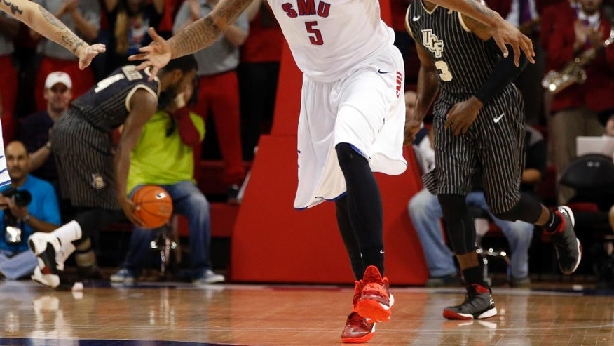 SMU forward Markus Kennedy (5) shouts after slam-dunking a ball during the first half of an NCAA college basketball game against Central Florida, Saturday, March 1, 2014, in Dallas. (AP Photo/John F. Rhodes)