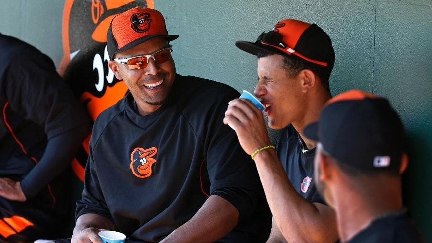 Baltimore Orioles' Nelson Cruz, left, take a break in the dugout with Manny Machado, center, after taking batting practice before an exhibition spring training baseball game in Sarasota, Fla.,  Saturday, March 1, 2014. (AP Photo/Gene J. Puskar)