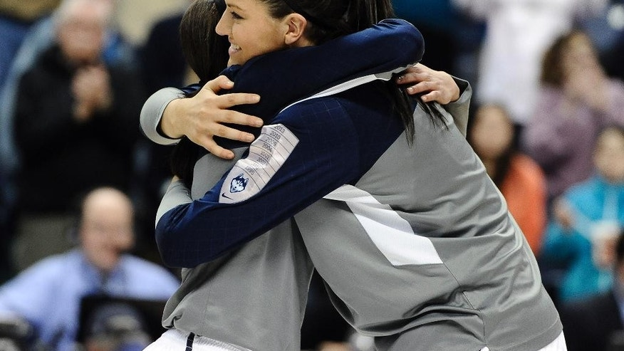 Connecticut's Bria Hartley, left, and Stefanie Dolson, embrace as they honored at senior night before an NCAA college basketball game against Rutgers, Saturday, March 1, 2014, in Storrs, Conn. (AP Photo/Jessica Hill)