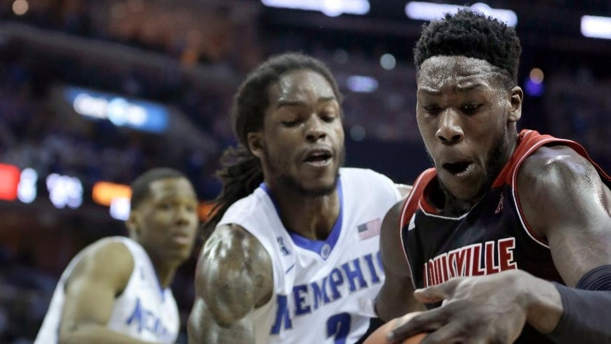 Louisville's Montrezl Harrell, right, is pressured by Memphis' Shaq Goodwin, center, in the first half of an NCAA college basketball game in Memphis, Tenn., Saturday, March 1, 2014. (AP Photo/Danny Johnston)