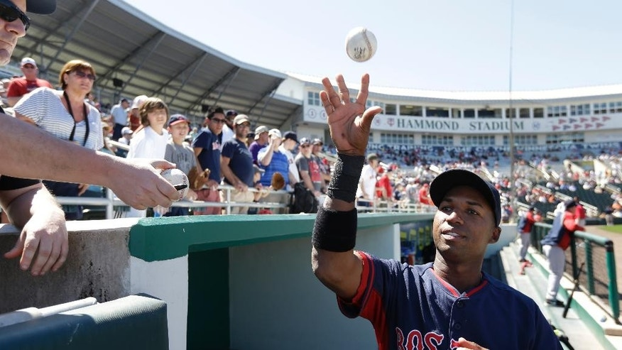 Boston Red Sox second baseman Jonathan Herrera, right, tosses a ball to a fan as he signs autographs before an exhibition baseball game against the Minnesota Twins, Saturday, March 1, 2014, in Fort Myers, Fla. (AP Photo/Steven Senne)