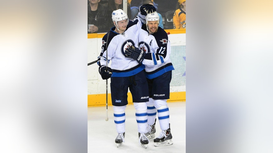 Winnipeg Jets defenseman Jacob Trouba (8) celebrates with Olli Jokinen (12), of Finland, after Jokinen scored a goal in the second period of an NHL hockey game against the Nashville Predators on Saturday, March 1, 2014, in Nashville, Tenn. (AP Photo/Mark Zaleski)