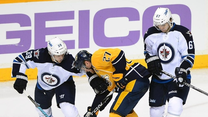 Winnipeg Jets defenseman Tobias Enstrom (39), of Sweden, and Michael Frolik (67), of the Czech Republic, battle Nashville Predators forward Patric Hornqvist (27), of Sweden, for the puck in the second period of an NHL hockey game on Saturday, March 1, 2014, in Nashville, Tenn. (AP Photo/Mark Zaleski)
