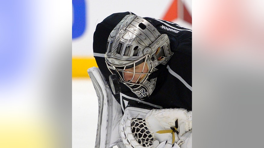 Los Angeles Kings goalie Jonathan Quick stops a shot with his mask during the first period of an NHL hockey game against the Carolina Hurricanes, Saturday, March 1, 2014, in Los Angeles. (AP Photo/Mark J. Terrill)