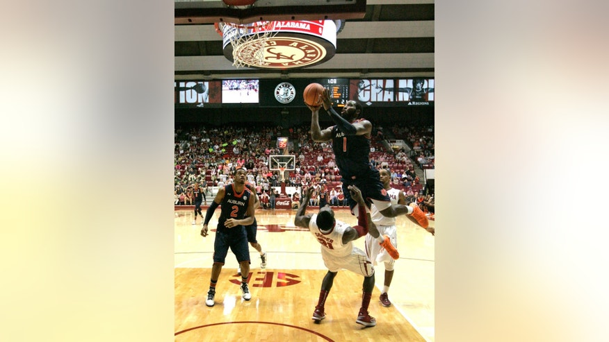 Alabama's Rodney Coper (21) draws a charge foul on Auburn's KT Harrell (1) as he goes up for a shot during the first half of an NCAA college basketball game on Saturday, Mar. 1, 2014, in Tuscaloosa, Ala. (AP Photo/Butch Dill)