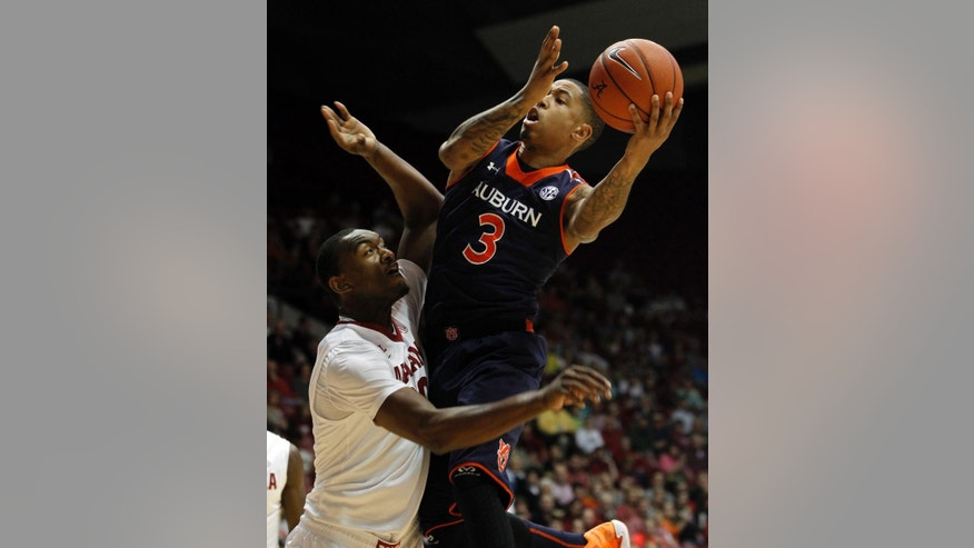 Auburn's Chris Denson (3) puts up a shot over Alabama's Jimmie Taylor (10) during the first half of an NCAA college basketball game on Saturday, Mar. 1, 2014, in Tuscaloosa, Ala. (AP Photo/Butch Dill)