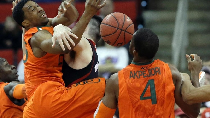 Miami's Garrius Adams, left, and Raphael Akpejiori (4) struggle with North Carolina State's Jordan Vandenberg for a rebound during the first half of an NCAA college basketball game in Raleigh, N.C., Saturday, March 1, 2014. (AP Photo/Gerry Broome)