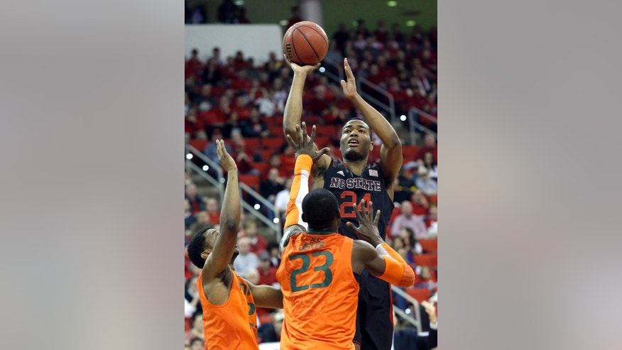 North Carolina State's T.J. Warren (24) shoots while Miami's Tonye Jekiri (23) and Garrius Adams, left, defend during the first half of an NCAA college basketball game in Raleigh, N.C., Saturday, March 1, 2014. (AP Photo/Gerry Broome)